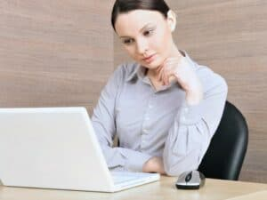 A woman in business attire in deep thought in front of a laptop computer